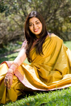yellow dress: indian woman sitting on grass