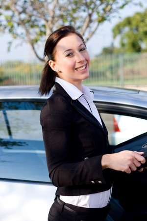 beautiful businesswoman standing next to a silver car photo