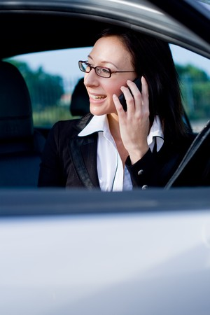 beautiful businesswoman in a silver car talking on cellphone photo