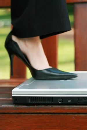 woman stepping on a laptop computer photo