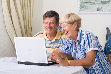 happy senior couple using laptop computer in living room photo