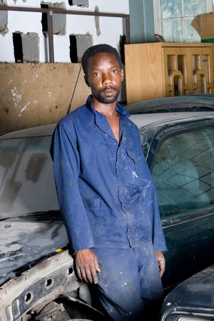 african mechanic resting in garage during lunch break photo