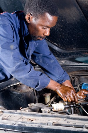 african mechanic working on a broken down vehicle photo
