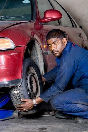 indian mechanic changing vehicle tyre photo