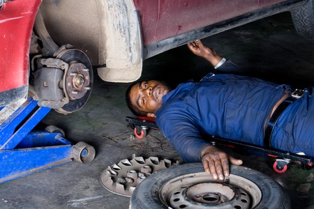 indian mechanic doing repair work on a vehicle photo