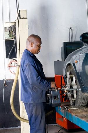 alineaci�n: african mec�nico trabajando en un veh�culo Foto de archivo