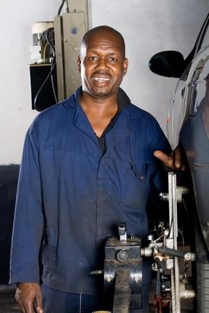blue collar: happy african mechanic portrait