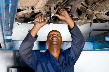 industrial mechanics: african mec�nico trabajando en un veh�culo Foto de archivo