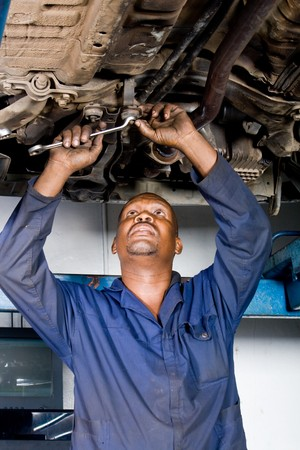 dirty man: african mechanic working on a vehicle