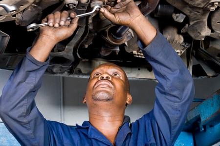 repair shop: african mechanic working on a vehicle