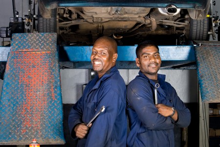 car in garage: two african mechanic in side garage Stock Photo