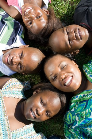 african mother, brothers and sisters lying on grass photo