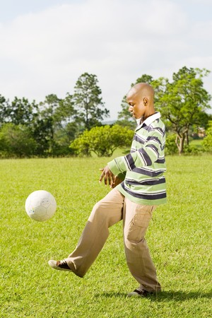 african american boy paly football in the park photo
