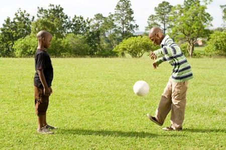 african boys paly football in the park photo