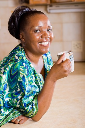 happy african woman drinking coffee in the kitchen photo
