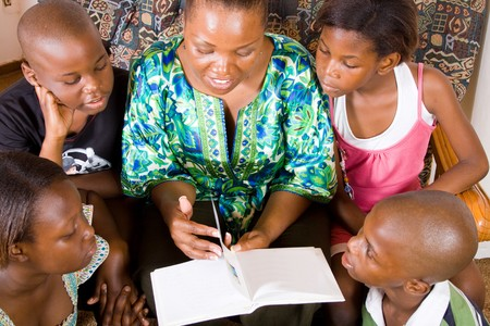 a happy african mother reading a book to her 4 children in living room Stock Photo - 4255591