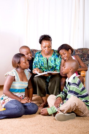 a happy african mother reading a book to her 4 children in living room photo
