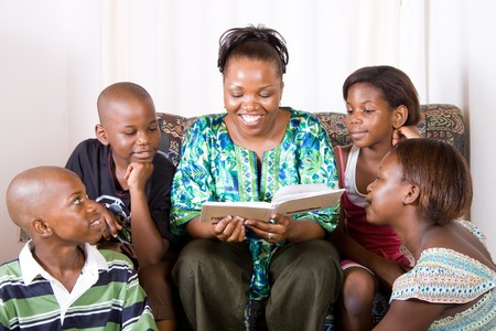 a happy african mother reading a book to her 4 children in living room Stock Photo