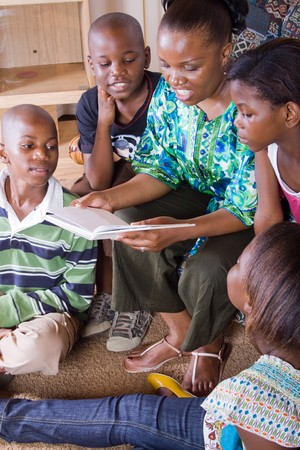 happy african mother reading a book to her 4 children in living room Stock Photo