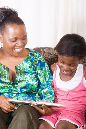 happy african mother reading a book to her daughter photo