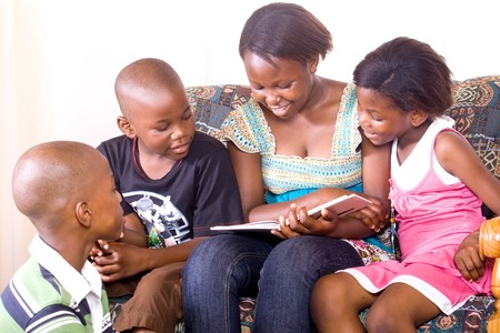 reading room: Elder african sister reads to her younger brother and sister Stock Photo