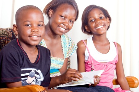 Elder african sister reads to her younger brother and sister photo