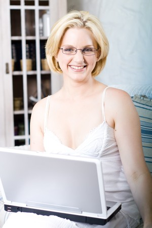 young woman sitting on sofa and using laptop photo