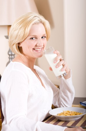 beautiful woman sitting by breakfast table and drinking glasses of milk photo