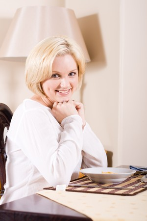 young blond beautiful woman sitting by breakfast table photo