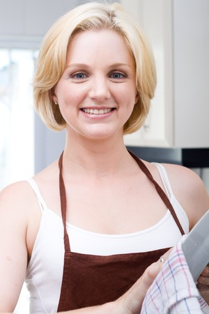 wash dishes: beautiful woman in the apron drying the dishes Stock Photo