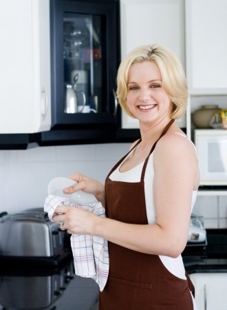 washing dishes: beautiful woman in the apron drying the dishes Stock Photo