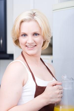 hermosa mujer rubia tomando jugo de naranja de nevera Foto de archivo - 4157357