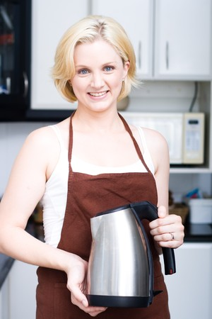 blond woman holding a kettle in the kitchen photo