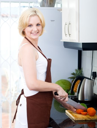 young blond woman cooking in kitchen photo