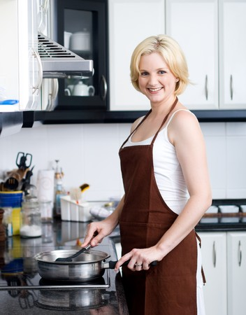 aprons: young blond woman cooking in kitchen Stock Photo