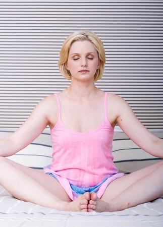 beautiful blond woman sitting on bed meditating photo
