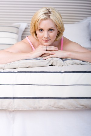 young beautiful happy woman on bed at bedroom photo