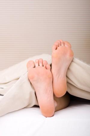 loosen up: Womans feet under the blanket