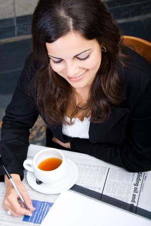 Joven mujer de negocios tomando t� y sonriente Foto de archivo - 4117001