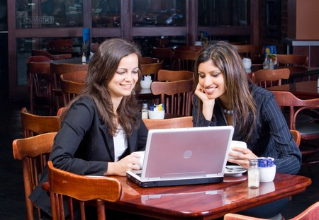 coffee meeting: two beautiful smiling businesswomen in cafe with laptop