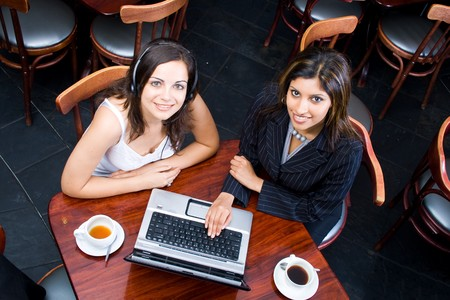 cafe shop: Overhead view of two business women meeting in a cafe Stock Photo