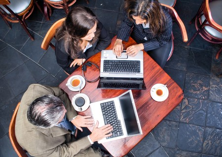 overhead: Overhead view of three business people meeting in a cafe