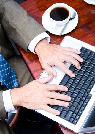 closeup of a business man typing on laptop computer photo
