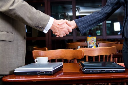 business man and woman shaking hands over two laptop Stock Photo - 4117147