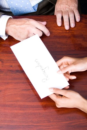 resignation: business woman handing in a letter of resignation to her boss