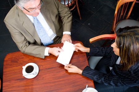 businesswoman handing in a blank envelope to her boss photo