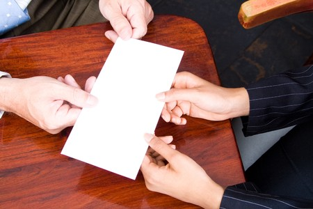 resignation: businesswoman handing in a blank envelope to her boss