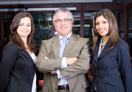 senior business man and two young business woman photo