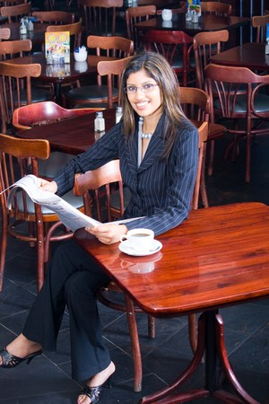 beautiful indian businesswoman reading financial newspaper in a cafe photo