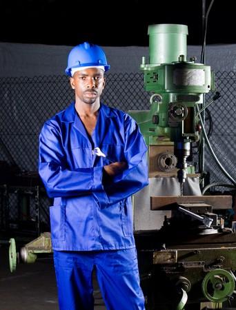 Afrikaanse machinist staande naast een boormachine